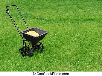 Spreader - Fertilizer spreader on green grass
