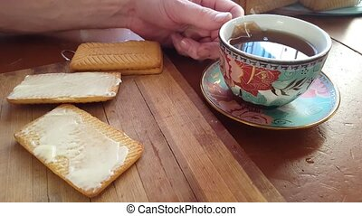 Spreading butter on a wheat cracker for breakfast with a...