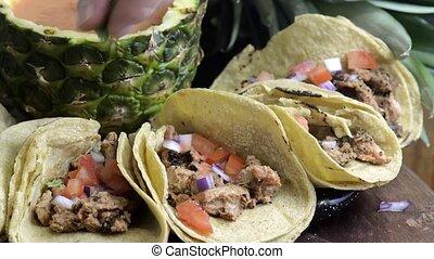 Spreading cilantro on tacos al pastor, Mexican food