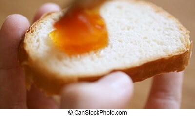 Spreading fruit jam on bread slice