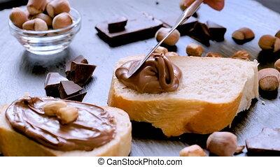 Spreading hazelnut chocolate cream on bread closeup....