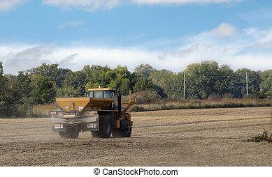 Spreading lime fertilizer onto a farm field