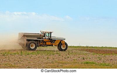 Truck spreading lime onto a farm field