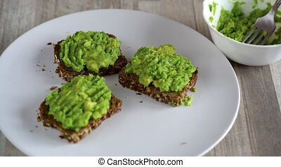 Spreading mashed avocado on toast and sprinkle with salt and...