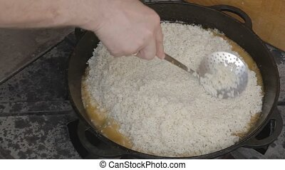 Spreading rice on cauldron and