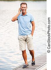 sprechende , bleiben, voll, everywhere., telefon, beweglich, gehen, quayside, während, fällig, berühren, länge, entlang, glückliches lächeln, mann