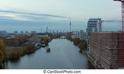Spree River with Berlin Cityscape and construction site on the riverside, Aerial wide angle forward dolly shot 4K
