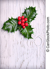 Sprig of christmas holly with red berries on vintage wooden background