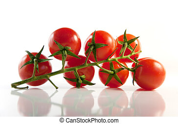 Sprig of ripe cherry tomatoes on a light background