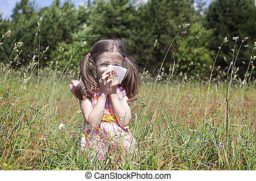 girl sneezing because of pollen allergy in a garden in the spring