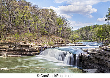 Whitewater flows over Indiana's Lower Cataract Falls under a cloudy blue spring sky.