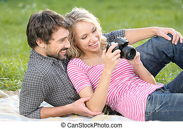 Spring at the pictures. Loving young couple is looking at the photographs they made on a picnic