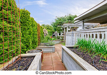 Spring backyard with garden beds and wood structures.