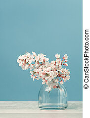 Spring blooming tree branches in a vase on tender soft blue