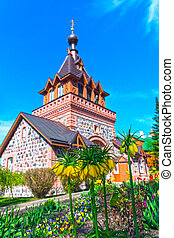 Spring blooming tulips against background of the brick Orthodox Church