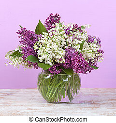 Spring bouquet. Lily of the valley and lilac in a vase