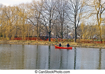 Spring Canoeists - Two canoeists in a red canoe on a spring ...