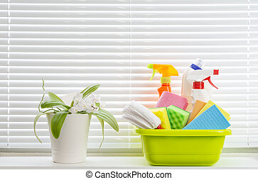 Spring cleaning concept with supplies against window background