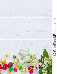 Spring concept. Colorful background of Easter with colored eggs on a wooden table with copy space. Flat lay. Top view with copy space.