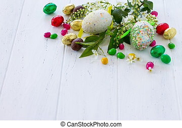 Spring concept. Colorful background of Easter with colored eggs on a wooden table with copy space.