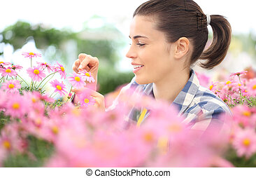 spring concept, smiling woman in the garden of daisies flowers