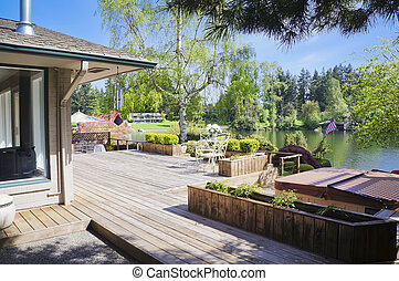 Spring deck and house view with lake and tub.