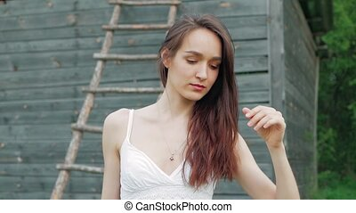 spring fashion portrait of a beautiful happy young woman in white dress with long brown hair near the wooden warehouse