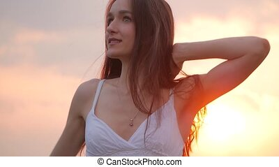 spring fashion portrait of a beautiful happy young woman in white dress with long brown hair on sunset background