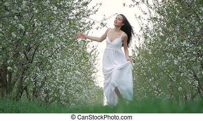 spring fashion portrait of a beautiful happy young woman in white dress with long brown hair run and enjoy the blossoming garden