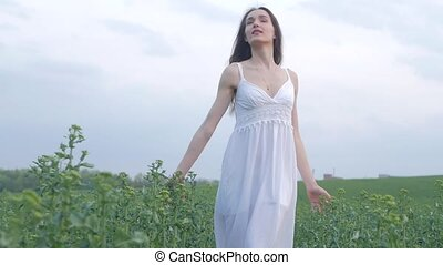 spring fashion portrait of a beautiful happy young woman in white dress with long brown hair walk the green field in the evening