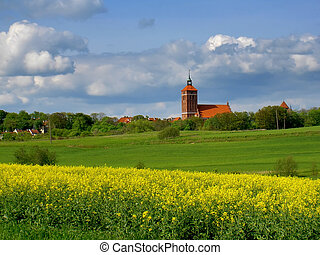 spring fields with old church