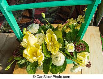 Spring flower arrangement in a green wooden box with a crossbar,