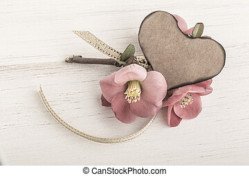 Spring flowers and heart shaped card on wooden background