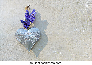 spring flowers and  iron heart hung on a outdoor wall