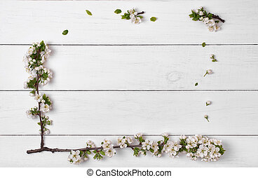 Spring flowers blossom frame on white wooden table background top view