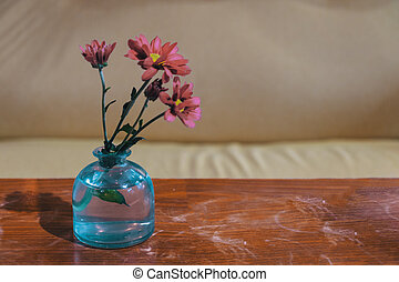 Spring Flowers In Blue Glass Bottle On Worn Wood Polished Table