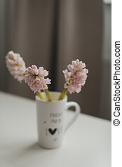 Spring flowers in cup on a table. Cozy home decor