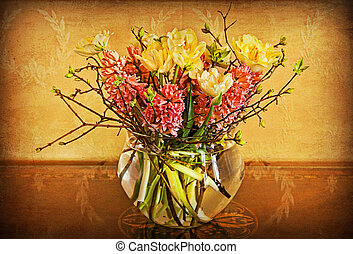 spring flowers in glass vase on grunge background