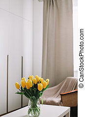 Spring flowers in living room interior. Bouquet of fresh yellow tulips on a table. Spring or holiday concept, March 8, birthday.