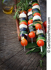 Spring garden barbecue. Vegetable kebabs with cherry tomatoes, zucchini, eggplant on wooden background