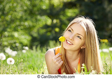 Spring girl lying on the field of dandelions daydreaming...