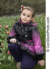 Spring girl sits in the meadow near the tulips.