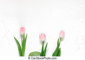 Spring greeting card with pink tulips and pink confetti on a white background and copy space. Mother's day, Valentine's day and women's international day on March 8
