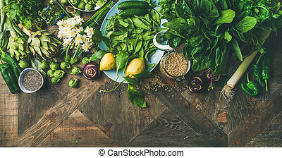 Spring healthy vegan food cooking ingredients. Flat-lay of vegetables, fruit, seeds, sprouts, flowers, greens over wooden background, top view, copy space, wide composition. Diet food concept