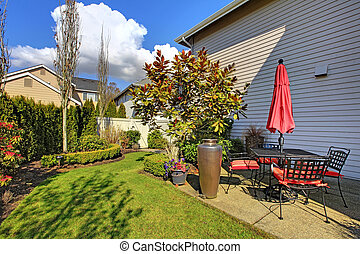 Spring house back yard with red chairs and umbrella and nice landscape.