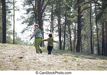 Spring in a pine forest with brother little sister holding hands.
