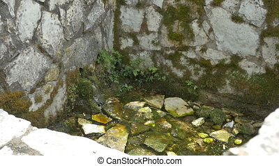 Spring in Stone Wall - Stone built stairs to a water spring.