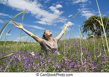 Beautiful young woman in meadow with wild purple flowers in bloom covered with butterflies on a sunny day with clear blue sky and white clouds