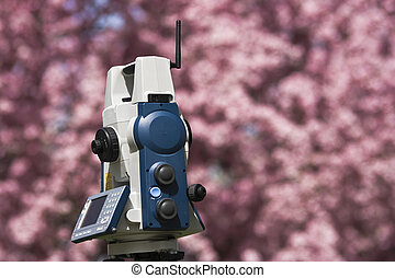 Spring Land Surveying - theodolite against blossoming tree