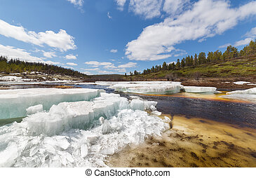 Spring landscape in Southern Yakutia during ice drift on a small stream